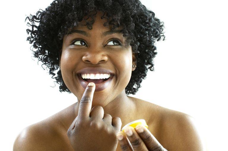 Woman putting on lip balm.