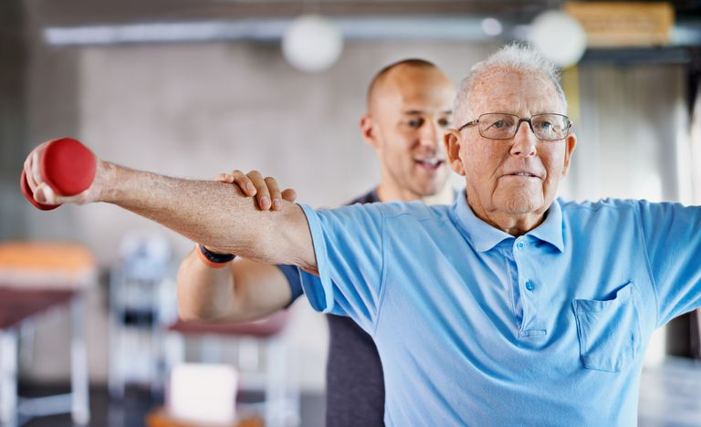 Shot of a physiotherapist helping a senior man with weights