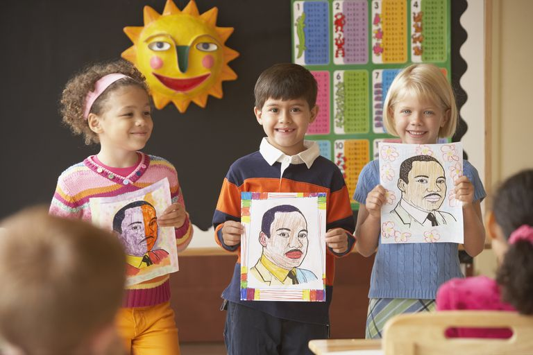 Group of young students holding up pictures in front of class