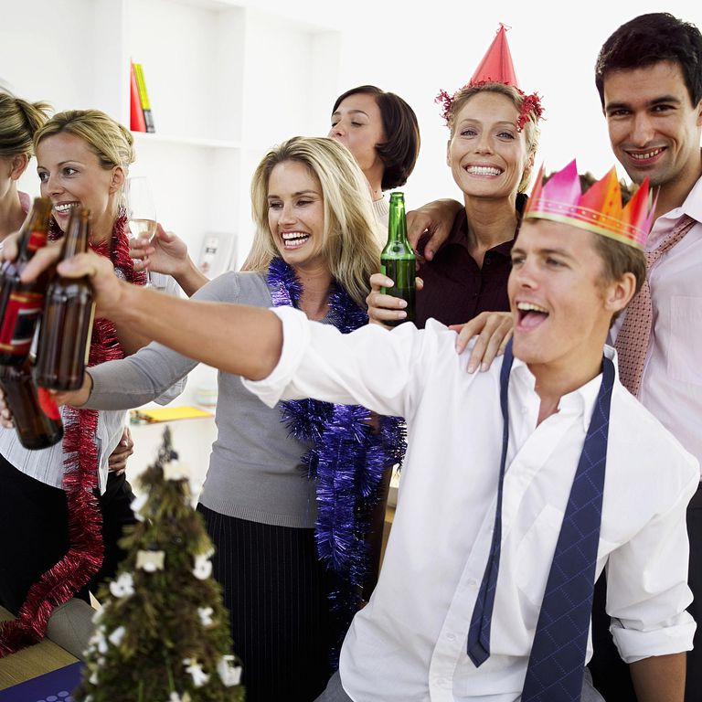 Young people raising drinks at a party