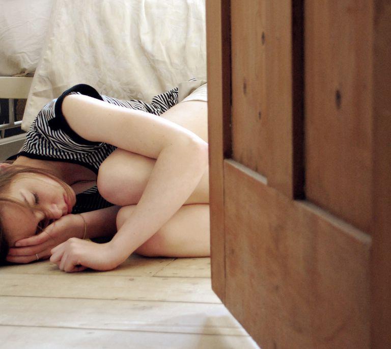 Sad girl curled up on floor