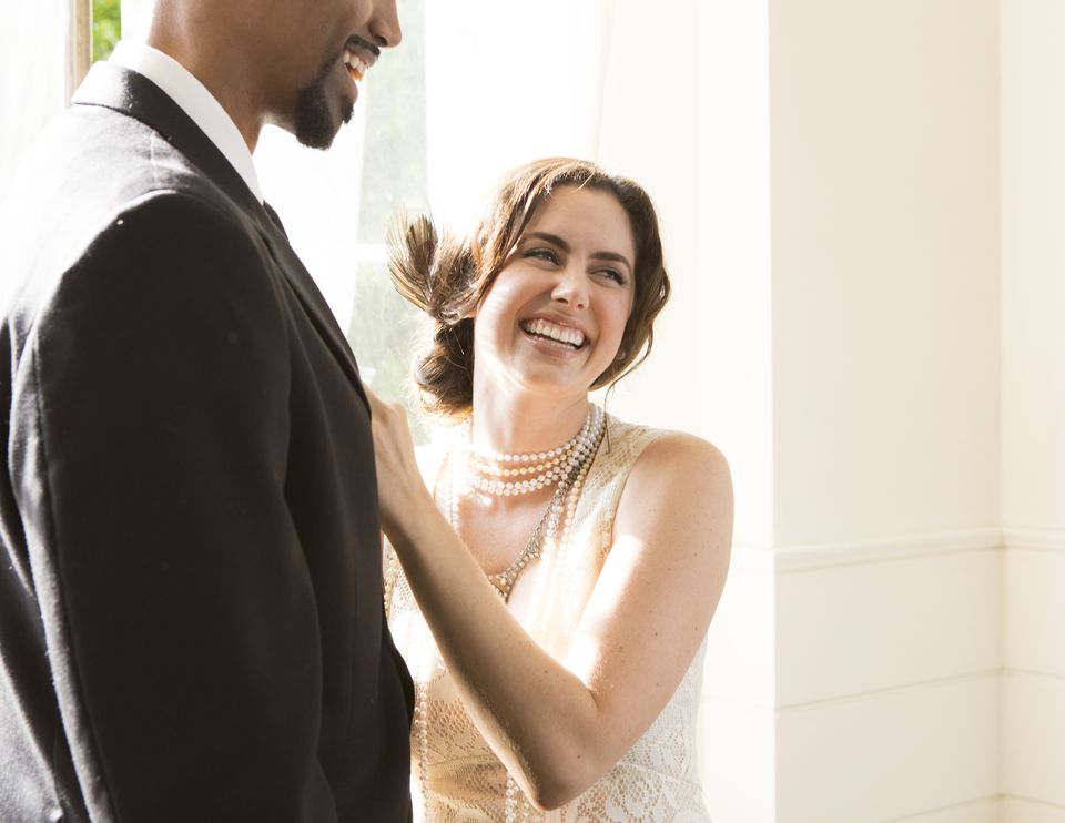 Bride Laughing while putting on Groom;s Boutinere