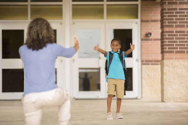 Mom reaches out to son on school steps.