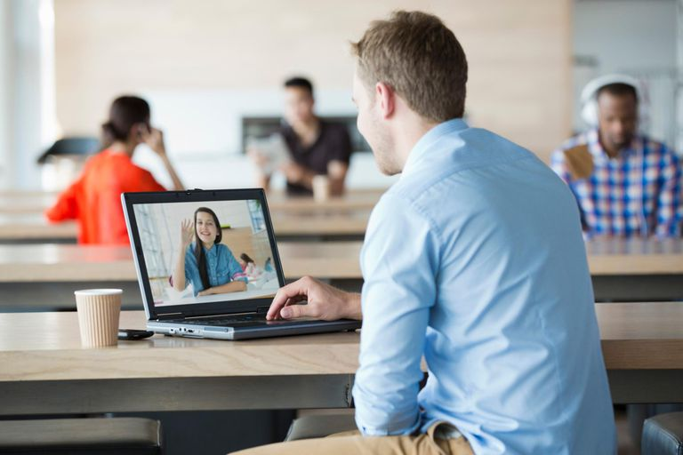 Young man using laptop to have video call with girlfriend