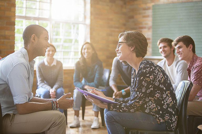 A woman practitioner councils a man in a group therapy session. Many applied and clinical sociologists work in the mental health field.