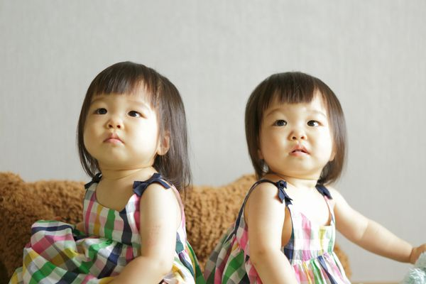 Twin girls in identical dresses sitting on a cough