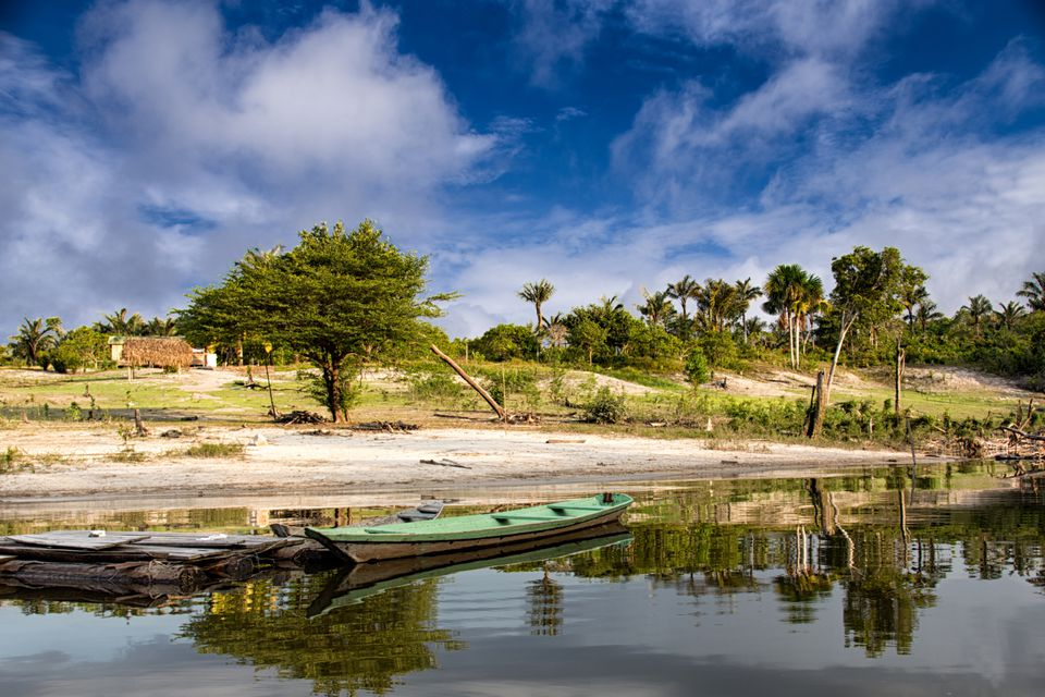 a small canoe lying on the shore of the Amazon river near Manaos, Brazil on a peaceful day in the jungle