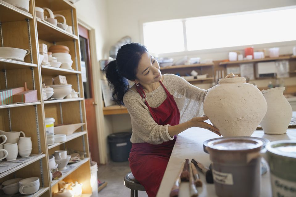 Female potter analyzing pot in studio