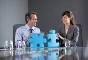 Business people fitting puzzle pieces together