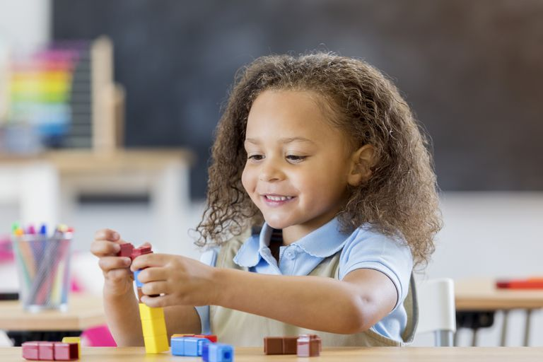 Confident African American child counts with counting blocks in her classroom.