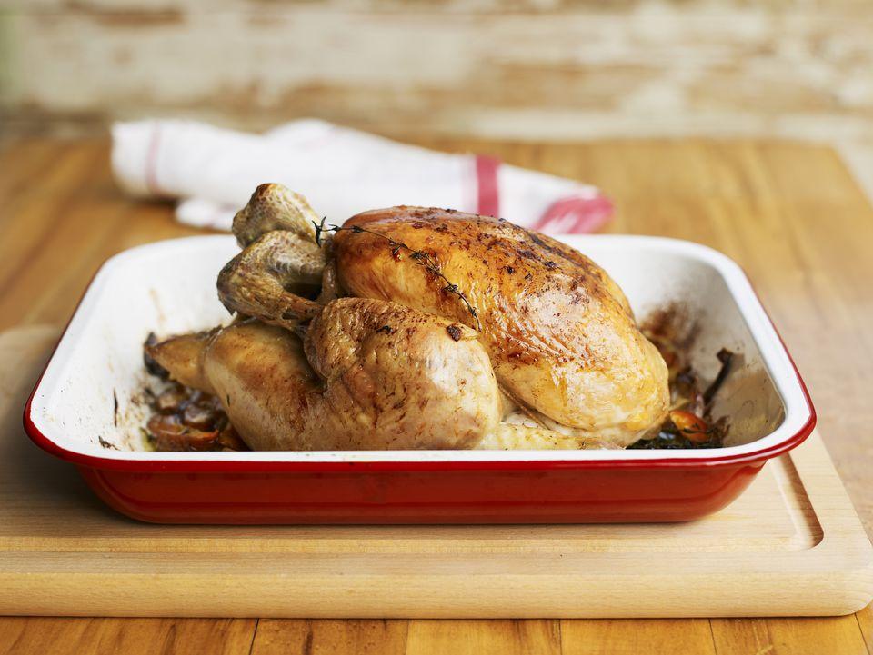 Whole roast chicken in roasting pan