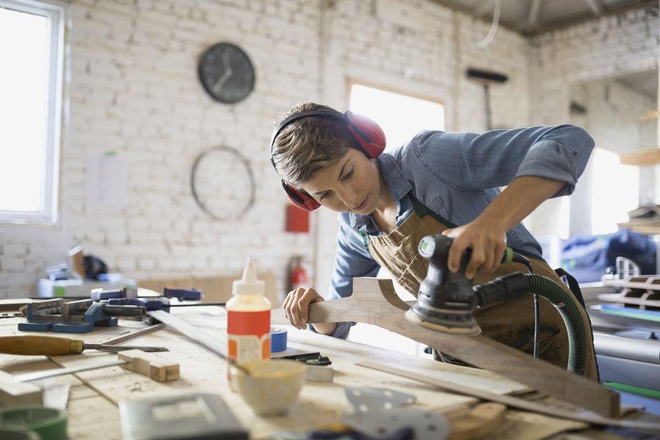 Female carpenter using sander on wood in workshop