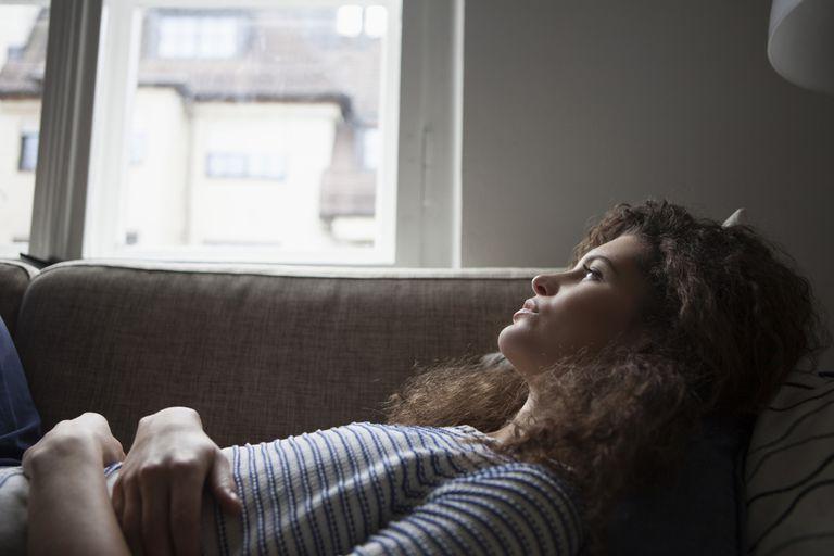 Serious young woman lying on sofa
