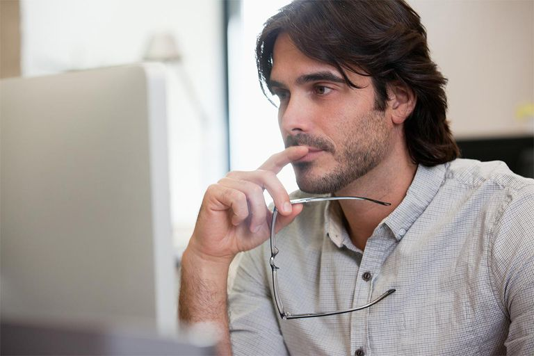 Pensive businessman working on computer in office