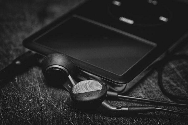 Close-Up Of Mp3 Player By In-Ear Headphones On Table