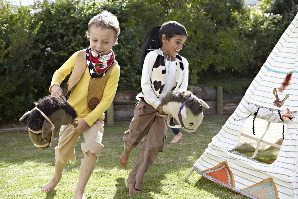 Boys playing cowboys in a garden
