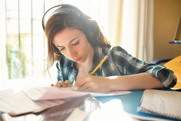 Woman in headphones writing on peice of paper