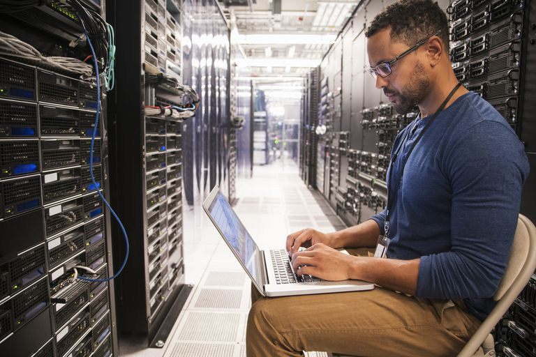 An IT technician uses a computer among racks of server.