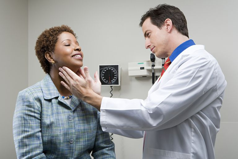 Doctor examining woman's thyroid