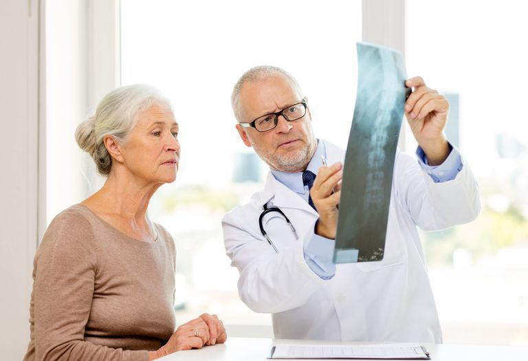 A doctors explains a woman's spine x-ray to her.