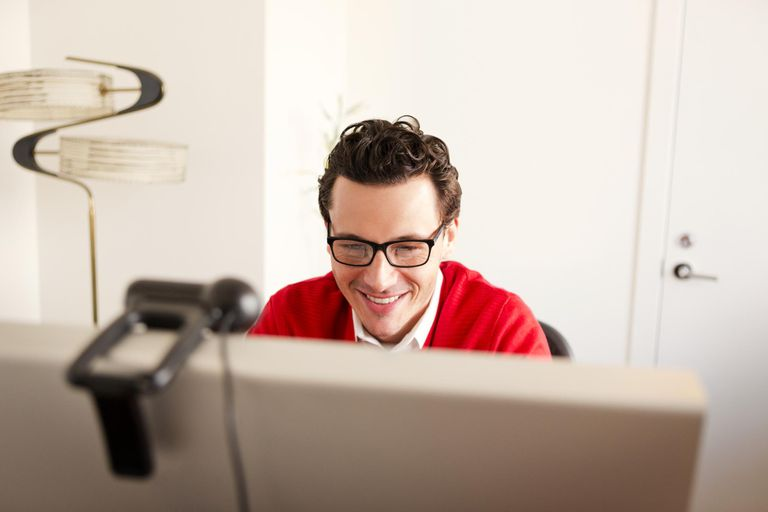 Man smiling while using a computer