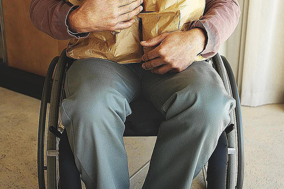Mid section view of a man sitting in a wheelchair holding bags of groceries