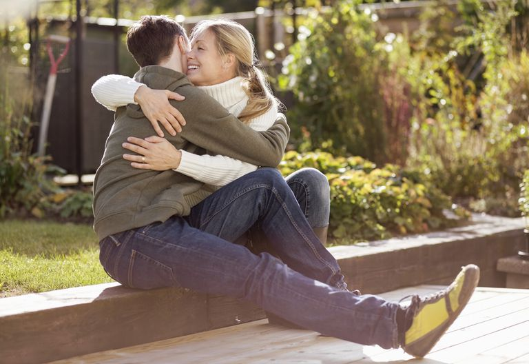 Mother and son embracing while sitting in garden