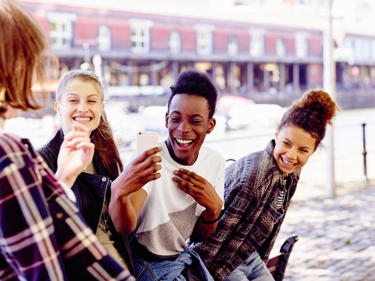 teen friends laughing and taking selfie