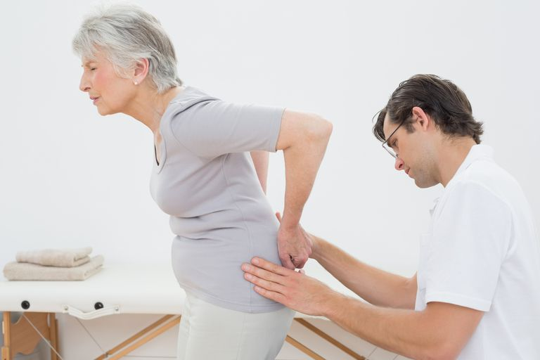 Senior woman being examined by physical therapist.