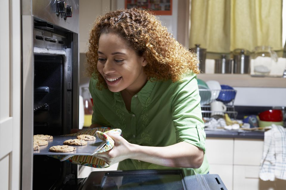 Woman taking cookies out of over, smiling