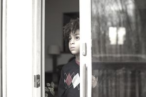 Young Boy Looking Out of Sliding Porch Door