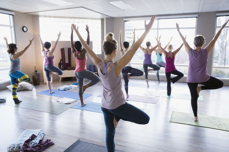 Women practicing tree pose in yoga class