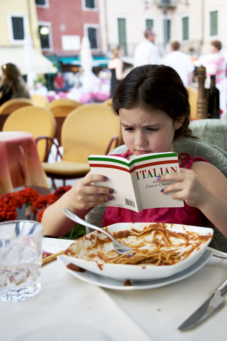 Girl reads Italian book after eating spaghetti