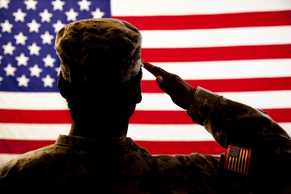 Solider saluting US flag