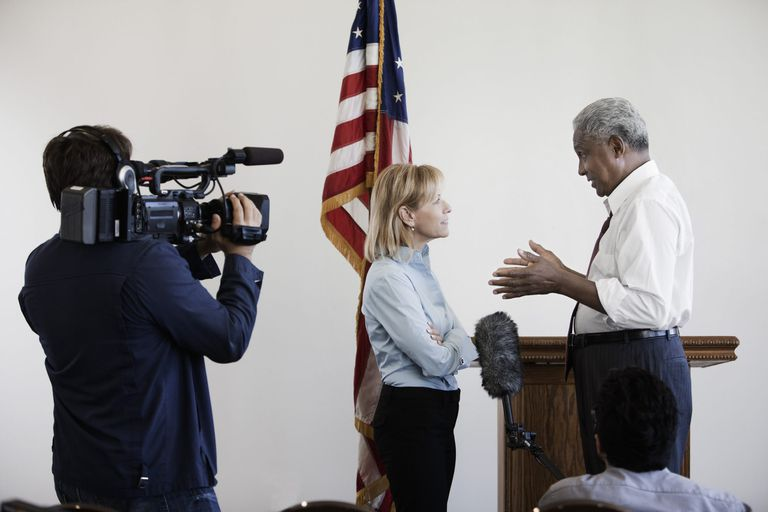 A picture of a politician being interviewed by a reporter