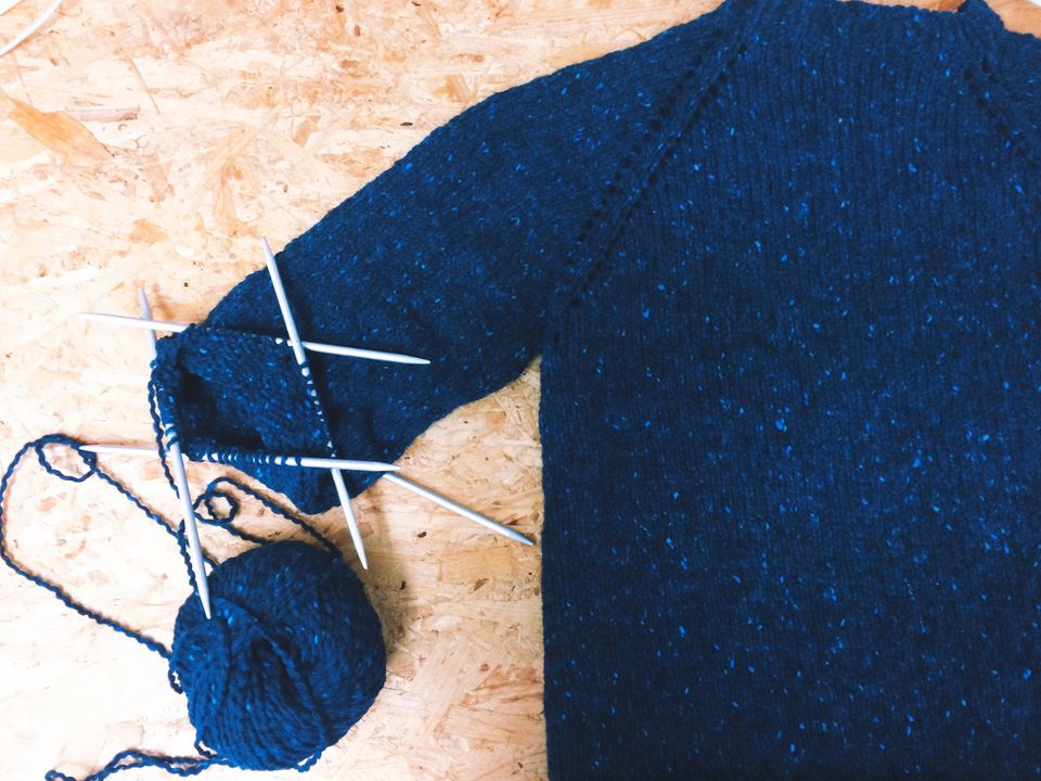 Close-Up Of Ball Of Wool With Knitting Needles And Sweater