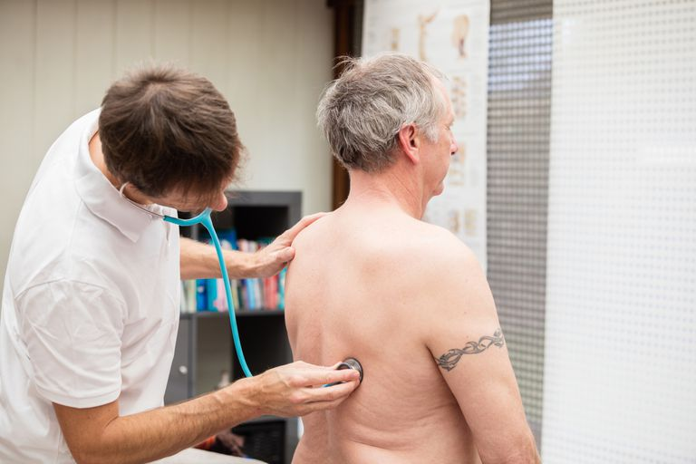 Doctor checking lung of mature patient