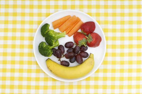 Banana, broccoli, carrot sticks, strawberries and grapes on plate, on yellow checked tablecloth