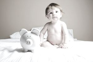 Baby sitting on bed with piggy bank