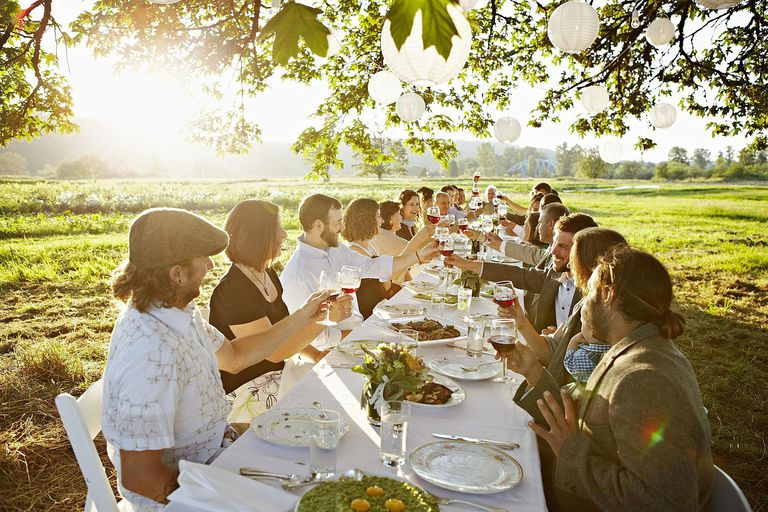 Group toasting at table outside in field