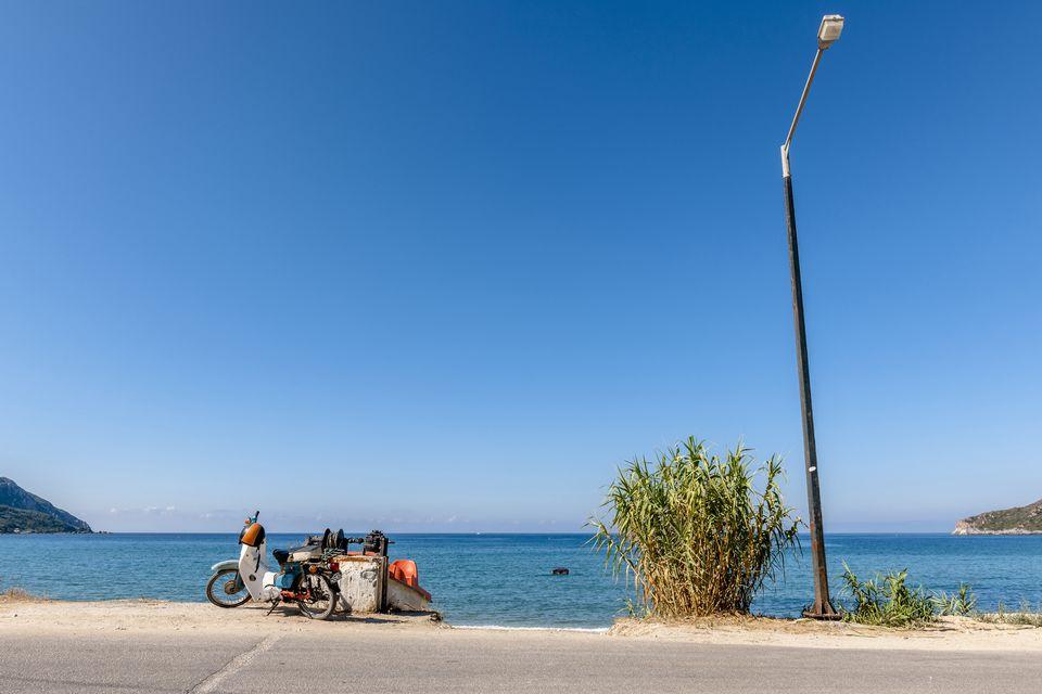 Greece, Corfu, Agios Georgios, moped and street lamp at the ocean