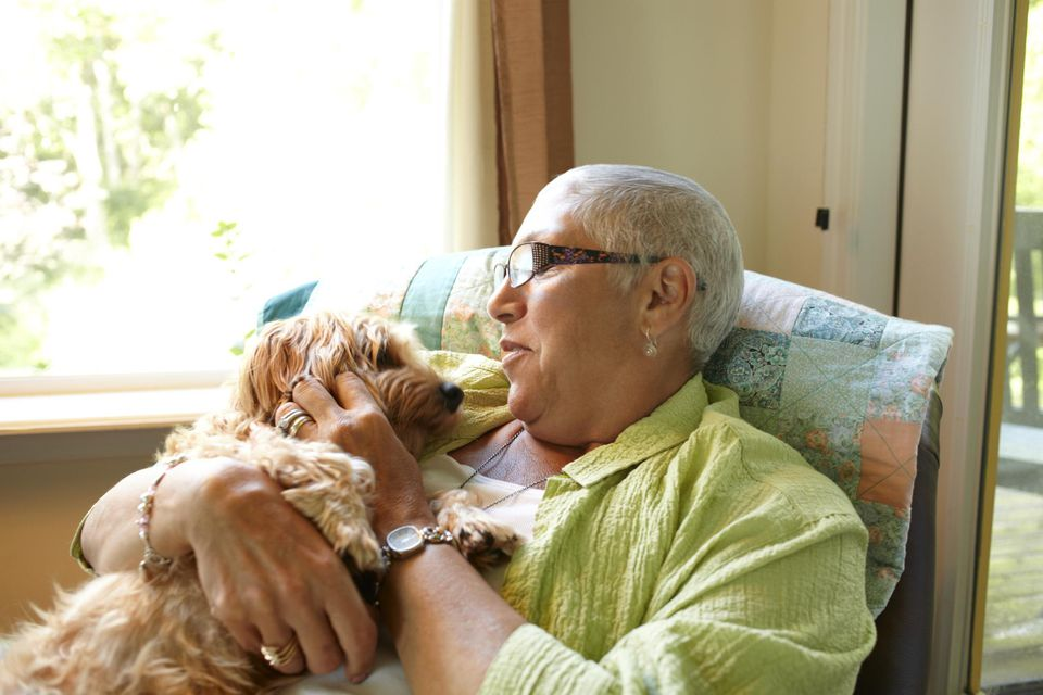 A caucasian woman holding a dog