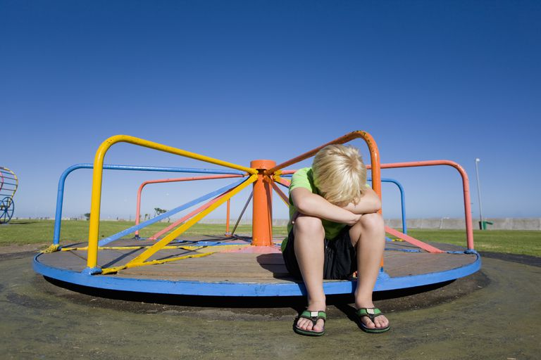 Frustrated boy sitting on still merry-go-round at playground