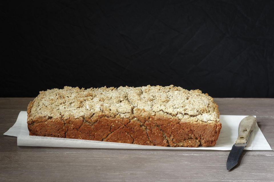 Home-baked buckwheat bread and kitchen knife on paper and wood