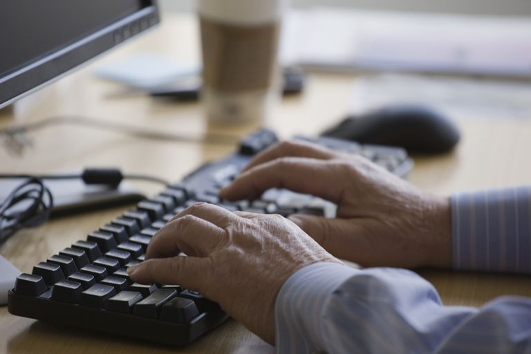 man typing on keyboard
