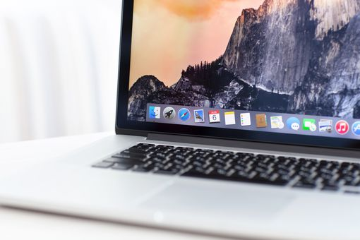 A Macbook Pro is open with on a white table, with a background of mountains on the screen.