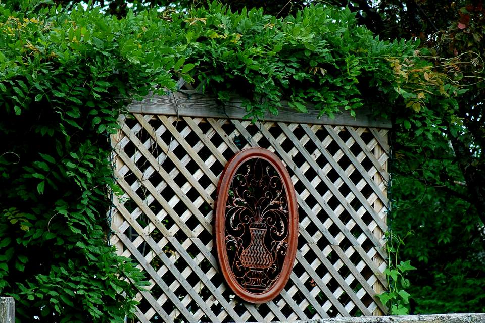 Lattice screen with medallion and vines growing over it.