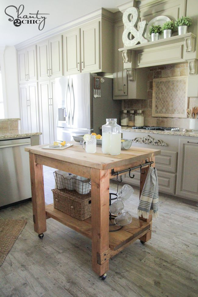 A wooden kitchen island on wheels.