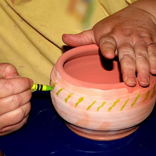 Crayon applied to a pot as a wax resist.