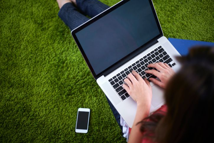 Woman on laptop on green rug